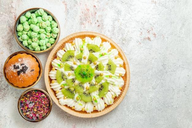 Widok z góry pyszny deser z pokrojonymi kiwi i cukierkami na białym tle ciasto herbatniki deserowe kremowe cukierki owocowe