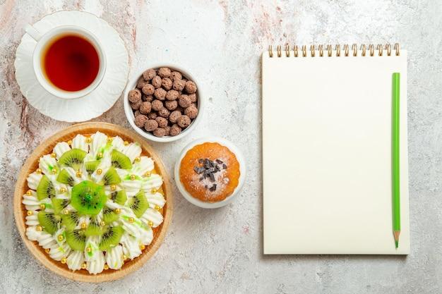Widok z góry pyszny deser z pokrojonymi kiwi i filiżanką herbaty na białym tle ciastko z kremem deserowym z cukierkami can
