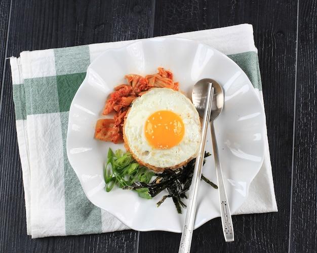 Widok z góry pyszny domowy ryż smażony z kupionym w sklepie marynowanym koreańskim kimchi lub ryżem smażonym kimchi