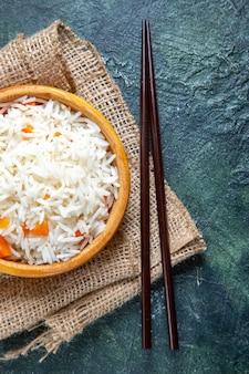Widok z góry pyszny gotowany ryż w małym talerzu na ciemnym biurku