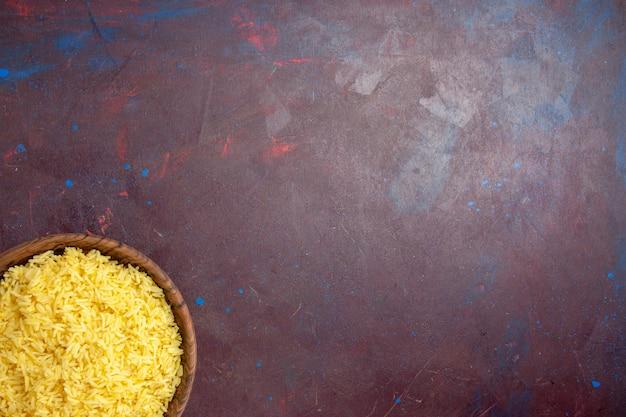 Widok z góry pyszny gotowany ryż wewnątrz brązowego talerza na ciemnym biurku