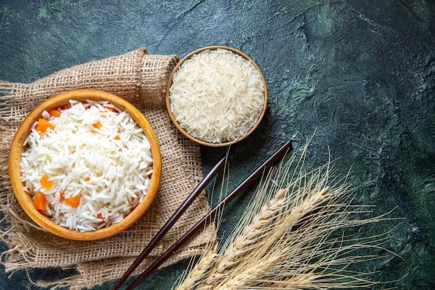 Widok z góry pyszny gotowany ryż z surowym ryżem w małym talerzu na ciemnym biurku