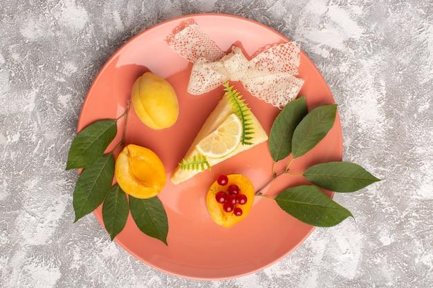 Widok z góry pyszny kawałek ciasta z cytryną i morelami wewnątrz różowego talerza na jasnym tle ciasto biszkopt słodkie ciasto piec