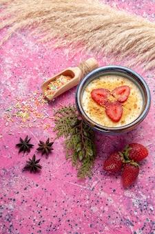 Widok z góry pyszny kremowy deser z czerwonymi plasterkami truskawek i ciasteczkami na jasnoróżowym biurku deser lody jagodowe słodkie owoce
