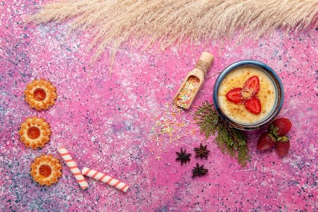 Widok z góry pyszny kremowy deser z czerwonymi plasterkami truskawek i ciasteczkami na jasnoróżowym tle deser lody krem jagodowy słodkie owoce