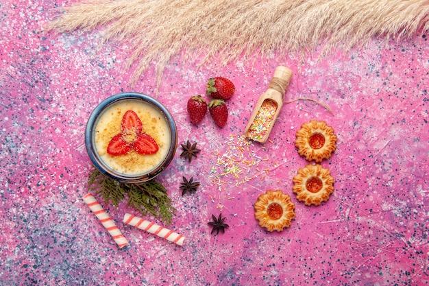 Widok z góry pyszny kremowy deser z czerwonymi plasterkami truskawek i ciasteczkami na jasnoróżowym tle deser lody słodkie jagody owoce
