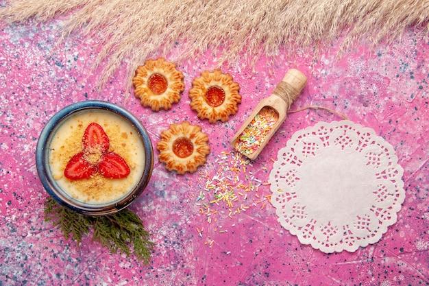 Widok z góry pyszny kremowy deser z czerwonymi plasterkami truskawek i ciasteczkami na jasnoróżowym tle deser lody słodkie owoce jagodowe