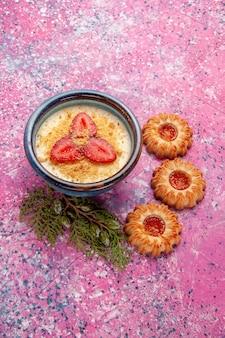 Widok z góry pyszny kremowy deser z czerwonymi plasterkami truskawek i ciasteczkami na różowym biurku deser lody w kolorze słodkiego lodu