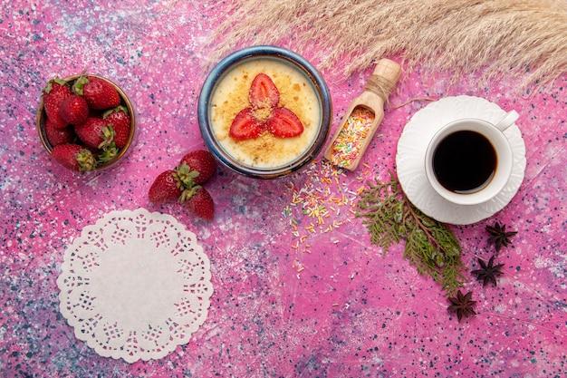 Widok z góry pyszny kremowy deser z czerwonymi plasterkami truskawek i filiżanką herbaty na jasnoróżowym biurku deser lody jagodowe słodkie owoce