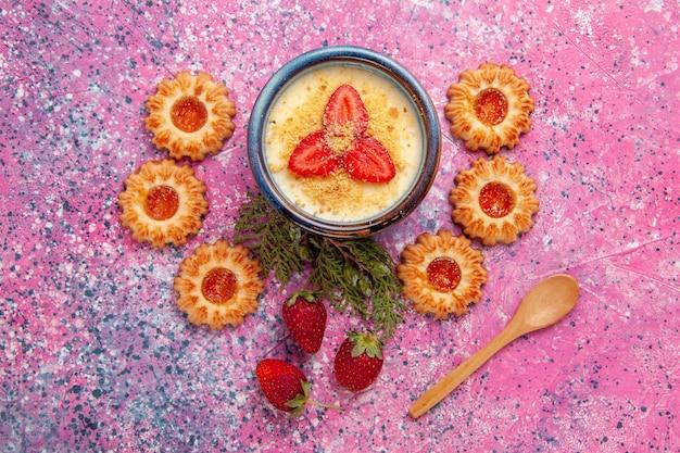 Widok z góry pyszny kremowy deser z czerwonymi pokrojonymi truskawkami i ciasteczkami na różowym tle deser lody lody słodki