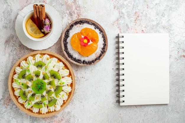 Widok z góry pyszny kremowy deser z filiżanką herbaty na białym biurku w kolorze cukierków na deserze śmietankowym