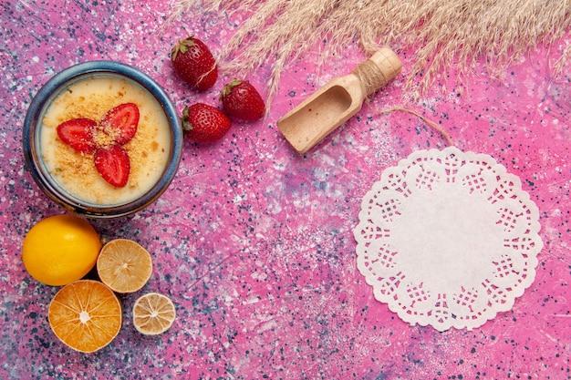 Widok z góry pyszny kremowy deser ze świeżą cytryną na jasnoróżowym tle deser lody jagodowe krem słodkie owoce