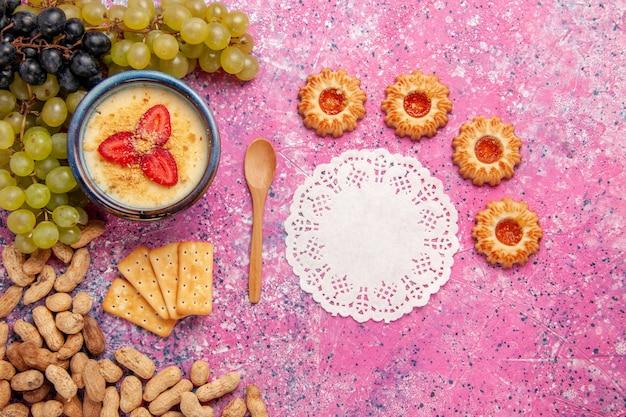 Widok z góry pyszny kremowy deser ze świeżymi ciasteczkami winogronowymi i orzeszkami ziemnymi na jasnoróżowym tle deser lody krem jagodowy słodkie owoce