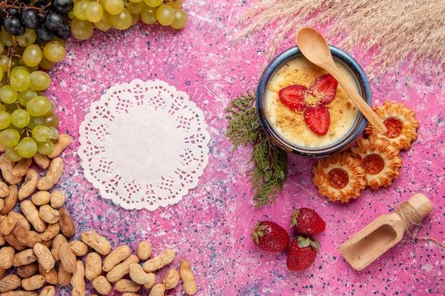 Widok z góry pyszny kremowy deser ze świeżymi ciasteczkami z zielonych winogron i orzeszkami ziemnymi na jasnoróżowym tle deser lody krem jagodowy słodki owoc