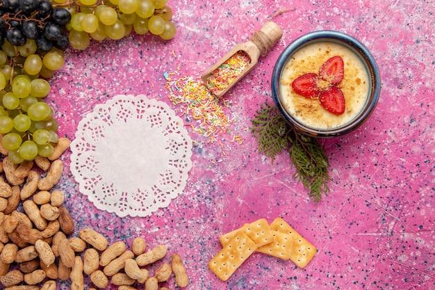 Widok z góry pyszny kremowy deser ze świeżymi krakersami winogronowymi i orzeszkami ziemnymi na jasnoróżowym tle deser lody krem jagodowy słodkie owoce
