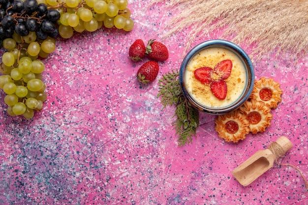 Widok z góry pyszny kremowy deser ze świeżymi zielonymi winogronami i ciasteczkami na jasnoróżowym tle deser lody jagodowe krem słodkie owoce