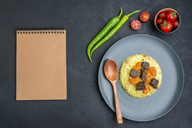 Widok z góry pyszny pilaw gotowany ryż z plastrami mięsa i pomidorami na ciemnej powierzchni