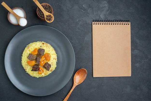 Widok z góry pyszny pilaw gotowany ryż z plastrami mięsa i przyprawami na ciemnej powierzchni