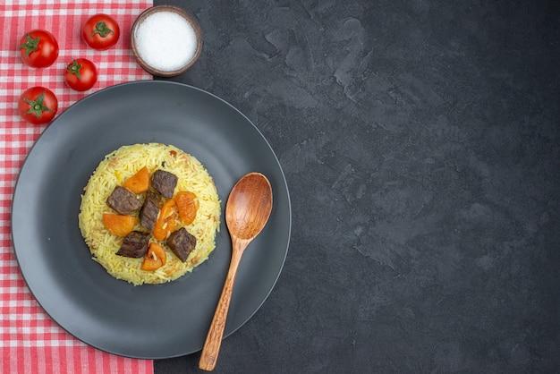 Widok z góry pyszny pilaw gotowany ryż z plastrami mięsa, solą i pomidorami na ciemnej powierzchni