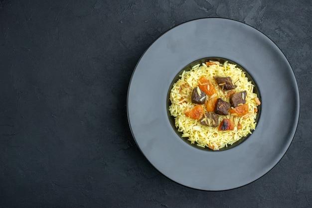 Widok z góry pyszny pilaw gotowany ryż z suszonymi morelami i plasterkami mięsa wewnątrz talerza na ciemnej powierzchni