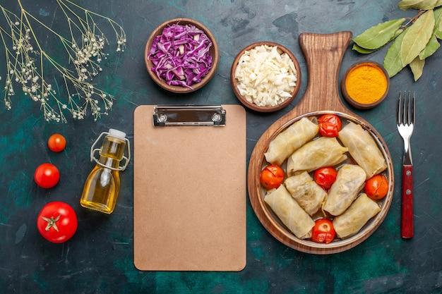 Widok z góry pyszny posiłek mięsny dolma zawijany z kapustą i pomidorami wraz z olejem na ciemnoniebieskim biurku jedzenie mięsne obiad potrawa warzywna gotowanie