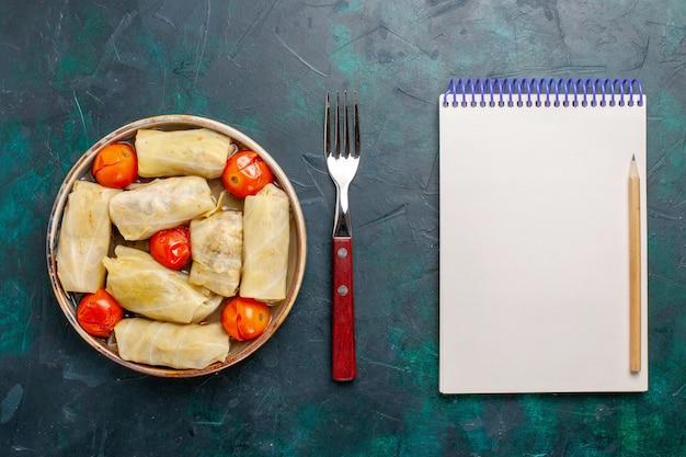 Widok z góry pyszny posiłek mięsny zawinięty w kapuście z pomidorami i notatnikiem na ciemnoniebieskim biurku mięso jedzenie obiad kalorie gotowanie warzyw