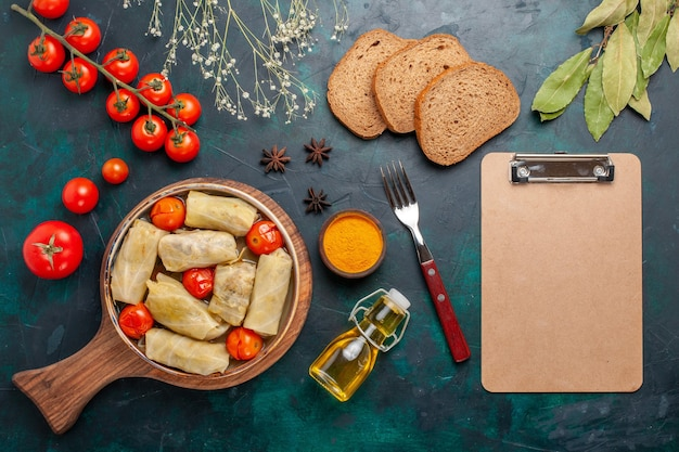 Widok z góry pyszny posiłek mięsny zawinięty w kapustę z chlebem olejowym i świeżymi pomidorami na ciemnoniebieskim biurku mięso jedzenie kolacja gotowanie warzyw