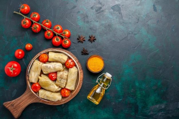 Widok z góry pyszny posiłek mięsny zawinięty w kapustę ze świeżymi pomidorami i olejem na ciemnoniebieskim biurku mięso jedzenie obiad kalorie gotowanie potraw warzywnych