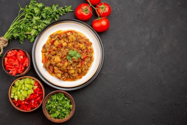 Widok z góry pyszny posiłek warzywny pokrojone w plasterki gotowane danie wewnątrz talerza na szarym biurku posiłek obiad jedzenie sos zupa warzywo