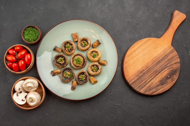 Widok z góry pyszny posiłek z grzybów ze świeżą zielenią i pomidorami na ciemnej powierzchni danie obiadowy posiłek gotowania grzyba