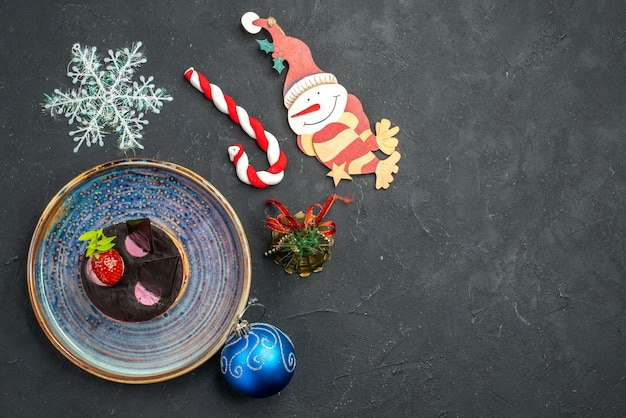 Widok z góry pyszny sernik z truskawkami i czekoladą na talerzu choinkowe zabawki na ciemnym odosobnionym tle wolne miejsce
