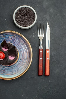 Widok z góry pyszny sernik z truskawkami i czekoladą na talerzu miska z czekoladowym widelcem i nożem na ciemnym tle na białym tle