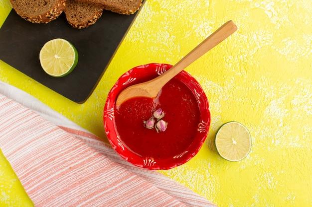 Widok z góry pyszny sos pomidorowy z cytryną i bochenkami chleba na żółtym stole zupa posiłek warzywny