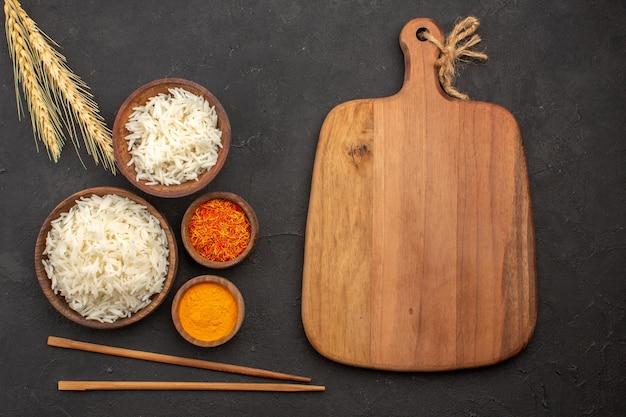 Widok z góry pyszny ugotowany ryż zwykły smaczny posiłek wewnątrz talerza na ciemnej przestrzeni