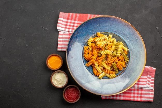 Widok z góry pyszny włoski makaron niezwykły ugotowany makaron spiralny na ciemnym tle danie makaronowe posiłek gotowanie obiad