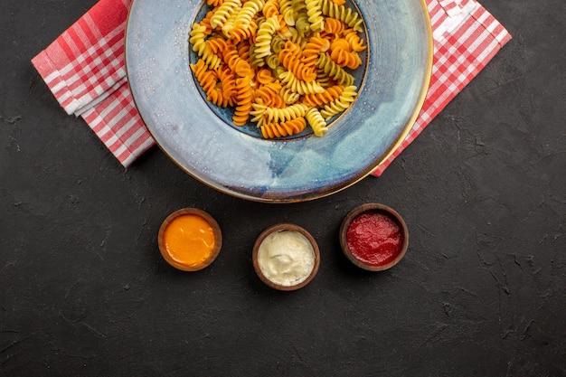 Widok z góry pyszny włoski makaron niezwykły ugotowany makaron spiralny wewnątrz talerza na ciemnym tle danie makaronowe obiad posiłek gotowanie