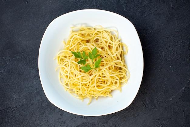 Widok z góry pyszny włoski makaron wewnątrz talerza na ciemnym tle makaron obiad posiłek gotowanie kuchnia ciemność kolor jedzenie