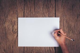 Widok z góry Ręka z pustym białym papierze