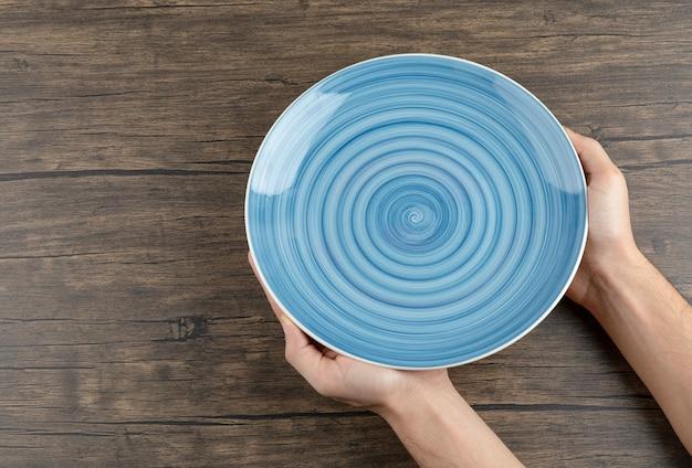 Widok z góry rąk człowieka trzymającego pusty niebieski talerz na drewnianym stole.