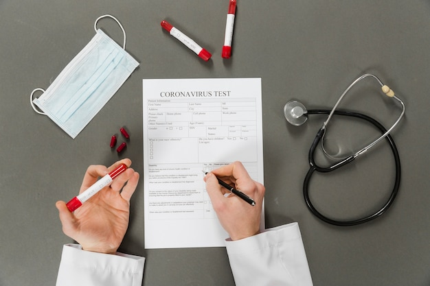 Widok z góry rąk lekarza wypełniającego test koronawirusa