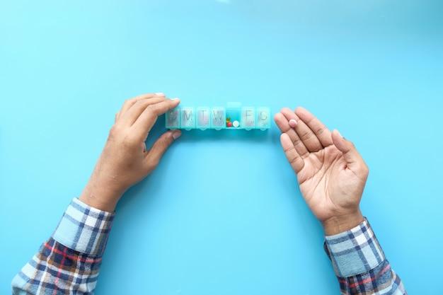 Widok z góry rąk mężczyzny biorącego lekarstwa z pudełka na pigułki