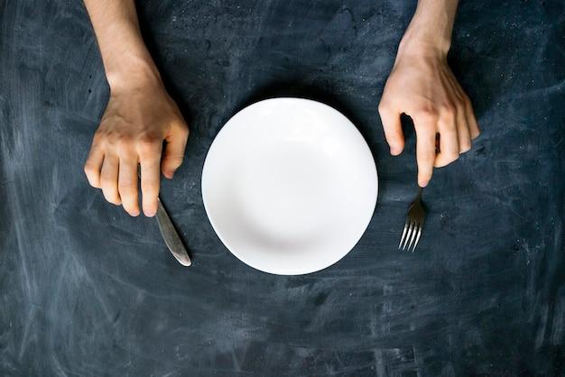 Widok z góry rąk osoby na stole z pustym talerzem