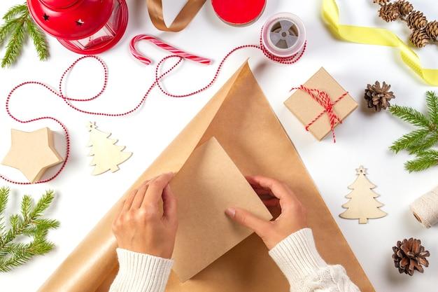 Widok z góry rąk pakujących prezent z różnymi instrumentami