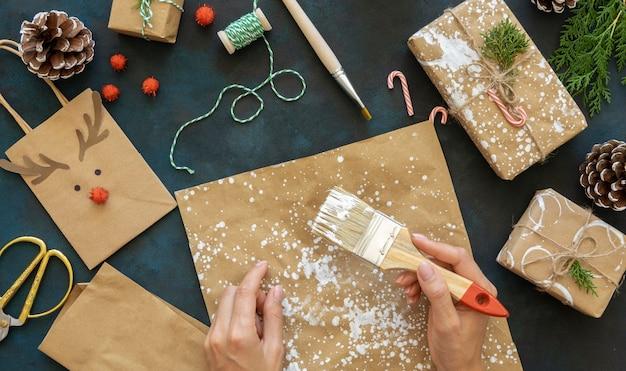 Widok z góry rąk za pomocą pędzla na świątecznym papierze do pakowania