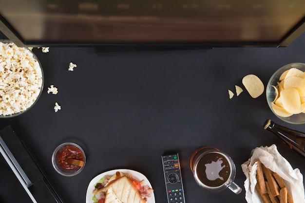 Widok z góry ramki akcesoriów i przekąsek dla graczy, mieszkanie leżał na czarnym tle z lato. joystick i gamepad, klawiatura, konsola do gier, mysz, telefon komórkowy, piwo, frytki i popcorn.