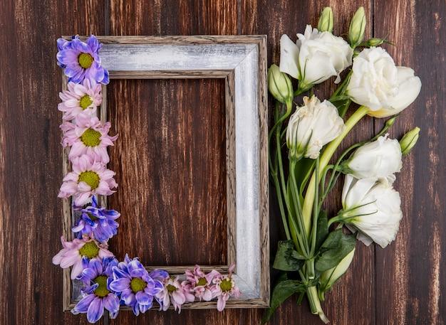 Widok z góry ramki i kwiatów na nim i na podłoże drewniane z miejsca na kopię