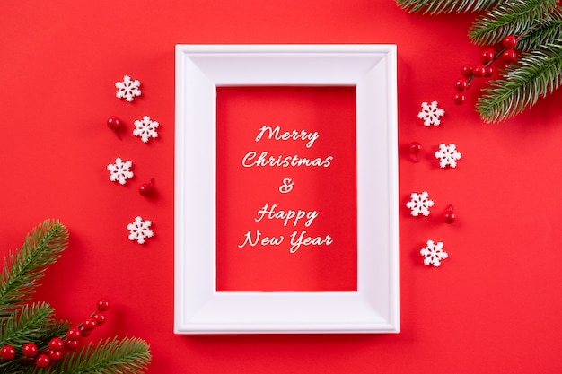 Widok z góry ramki na zdjęcia, płatki śniegu, czerwone jagody i ozdoby choinkowe na czerwonym tle z tekstem.