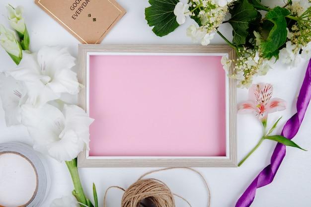 Widok z góry ramki na zdjęcia z różową kartką papieru, małą kartką pocztową i kwiatem mieczyk w białym kolorze oraz gałęzi kwitnącego kaliny na białym tle