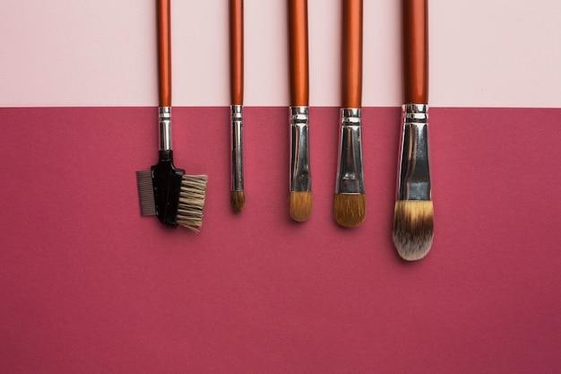Widok z góry ramki z pędzlami do makijażu i różowym tle