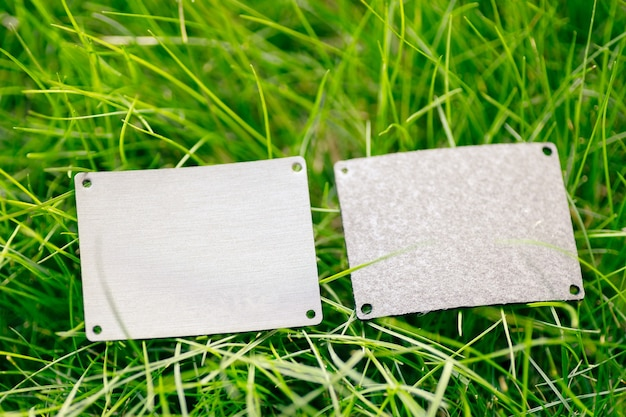 Widok z góry ramy wykonanej z zielonej wiosennej trawy i dwóch szarych skórzanych łatek na sprzedaż z miejscem na kopię na logo. naturalna koncepcja.